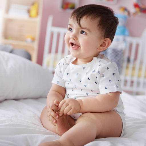 smiling baby on a white bed