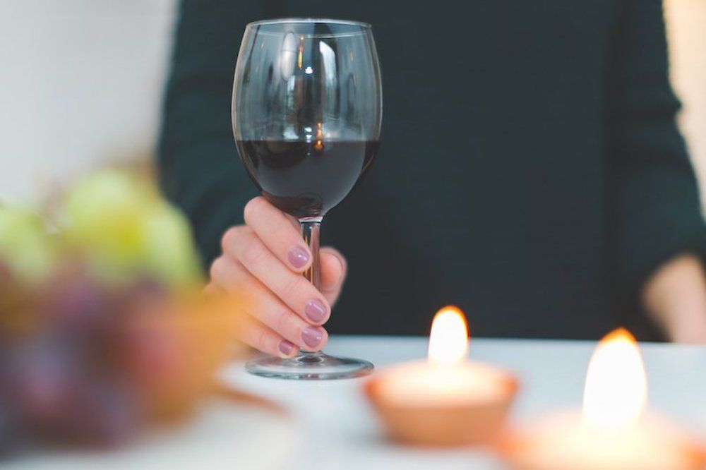 an image of a man holding a glass of red wine