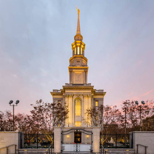 Photo of the Philadelphia Temple glowing against a blue and pink sky.