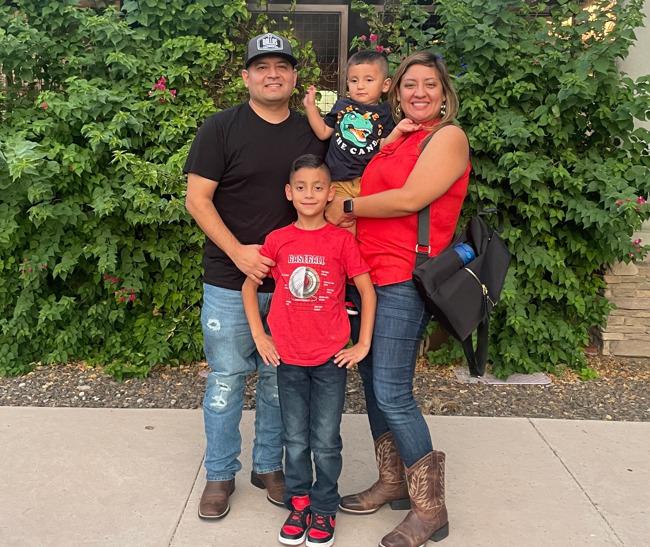 Family of 4 in front of flower bush