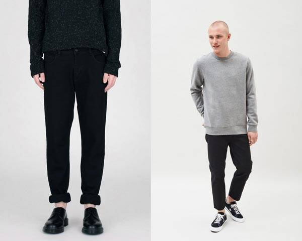 Man wearing black rolled up organic cotton jeans with black derby jeans and man wearing grey sweatshirt with black jeans and black converse