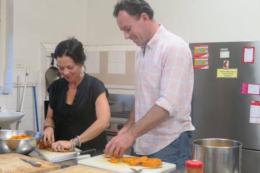 Two sevites preparing vegetables in kitchen