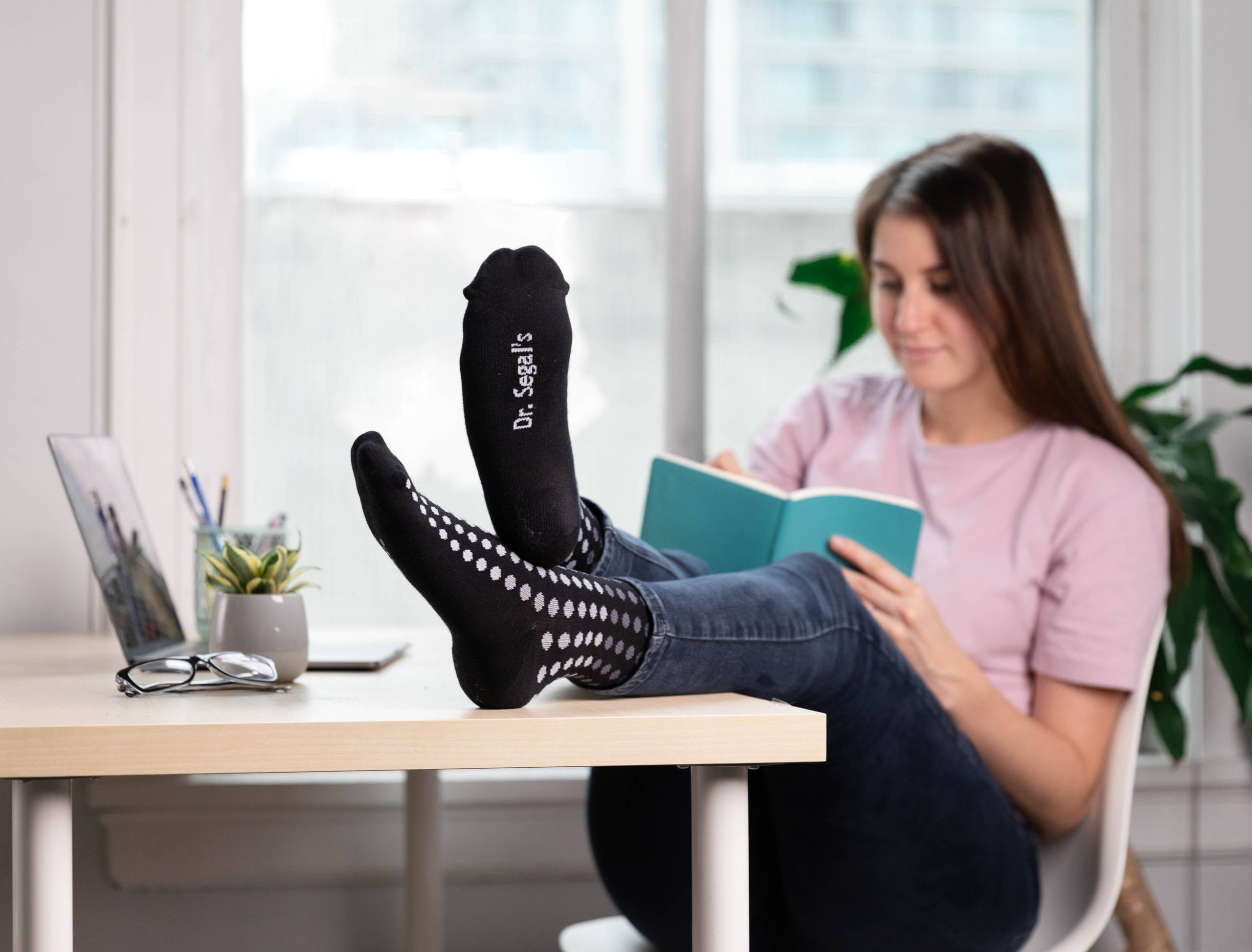 "Person sitting in chair reading a book with feet up on desk. Socks are black with white and grey dots. Socks say ""Dr. Segal's' on the bottom."