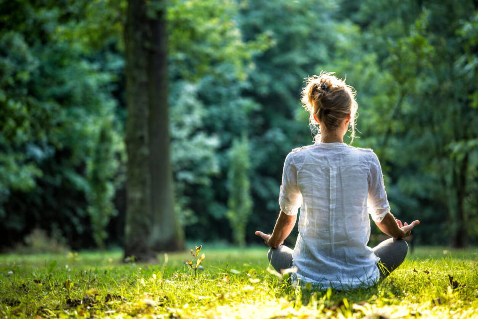 Woman meditating surrounded by trees