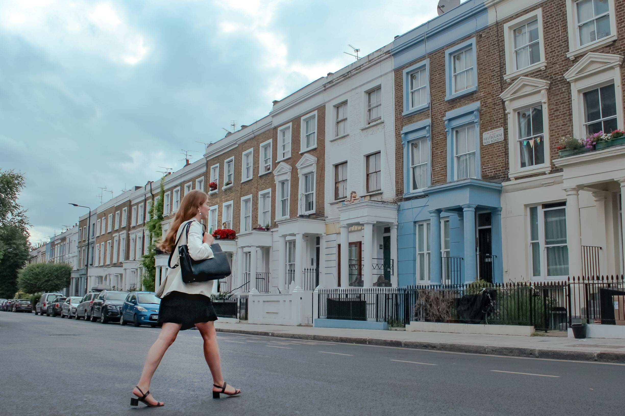 Business women crossing the street carrying a shoulder bag in Notting Hill
