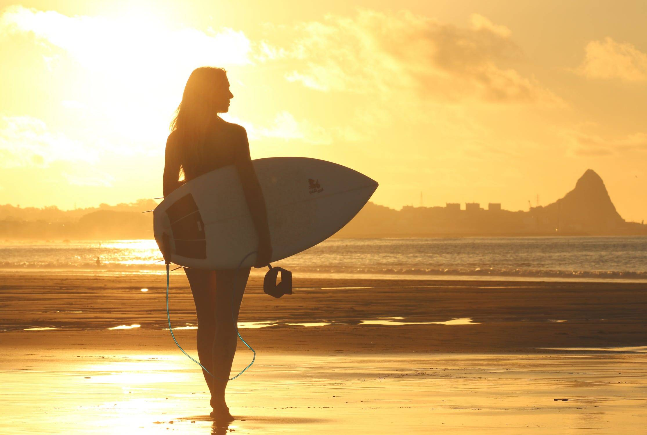 surfer girl in the beach sunset
