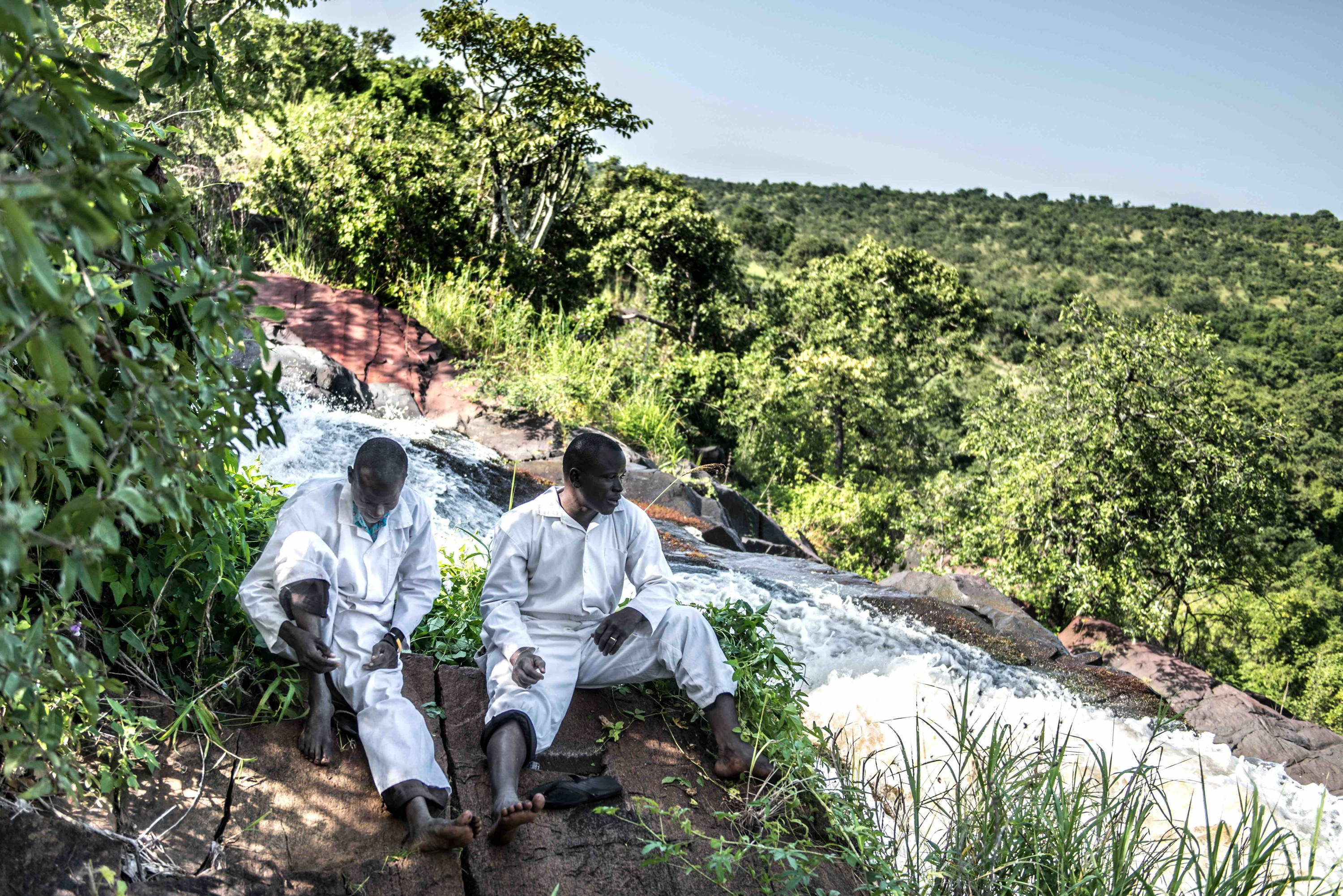 Members of a team assigned to capture black flies as part of a river blindness elimination program wait at their usual collecting spot at Aruu falls on the Agongo river