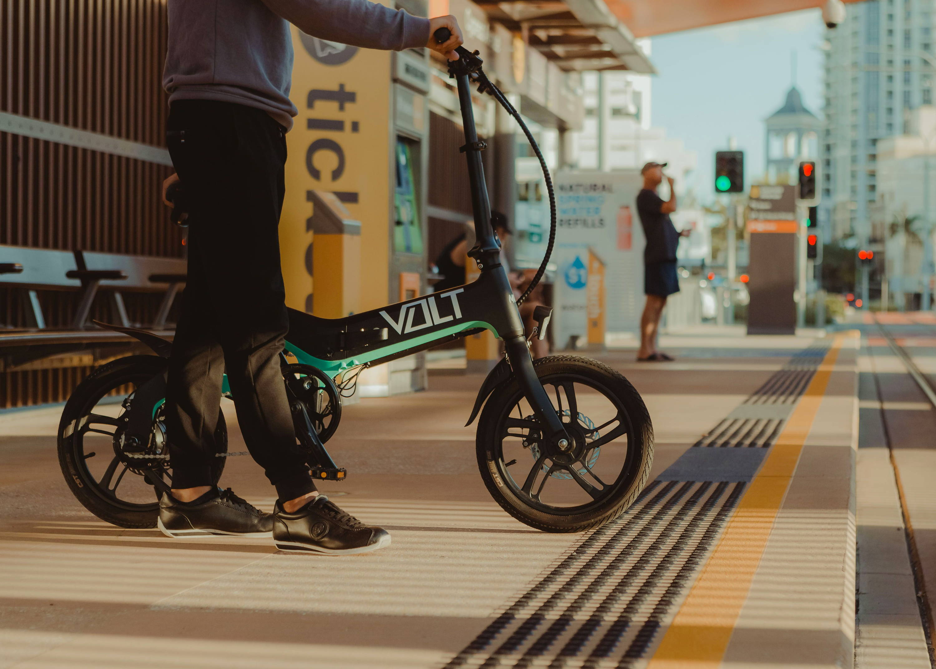 Man waits for tram with the VOLT Mate e-bike. The VOLT Mate electric bicycle can fold to take on public transports. it's 10 second folding design allows it to be quickly and conveniently taken onto trains, buses, trams and ferries alike. VOLT folding electric bikes can be used with public transport. VOLT ebikes can also fold and fit into the back and trunk of passenger cars. unique 3 step folding mechanism with removable and lockable battery means the VOLT mate is the most agile electric bike for sale.