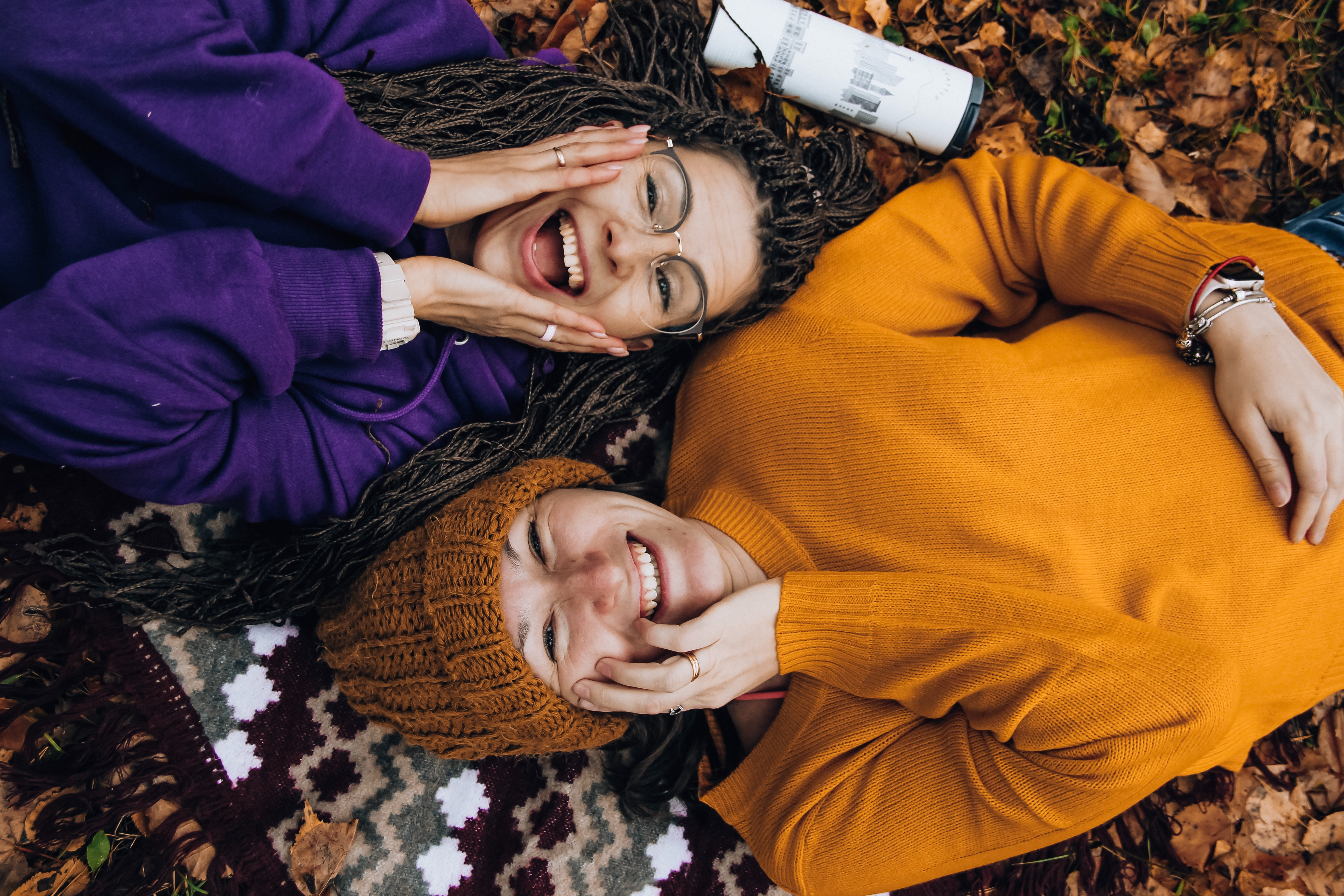 Image of two women wearing long sleeve sweaters lying on the ground together. Both have a smiling and surprised expression on their faces and are on a blanket.