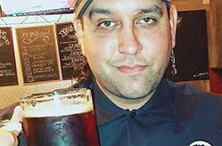 Josh is smirking while cheersing the camera with a stein full of dark lager. He is wearing a hat, so his mohawk can not be seen and he has one dangling earring visible.
