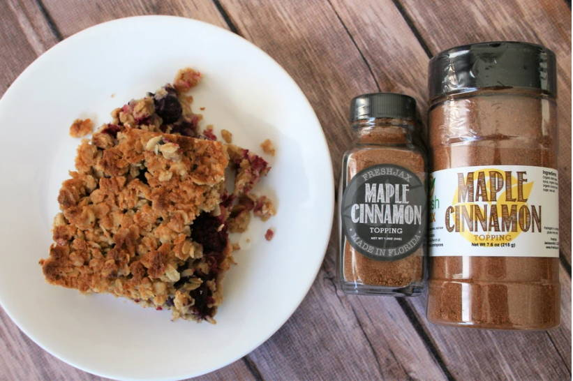 A plate of maple cinnamon yoga bars next to two bottles of FreshJax's Organic Maple Cinnamon Topping.