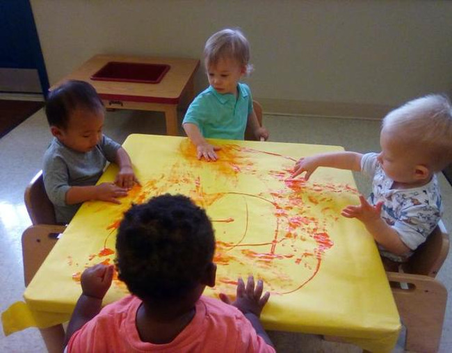 Toddlers sitting with paint