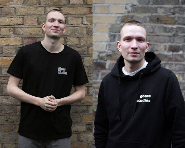 Man wearing organic cotton black oversized hoodie with white large printed logo with Goose Studios text and man wearing black organic cotton short sleeve t-shirt, both on a brick wall background