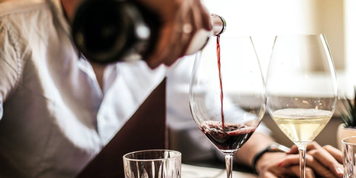 Man pouring red wine into a glass highlighting the importance of vision during tasting wine.