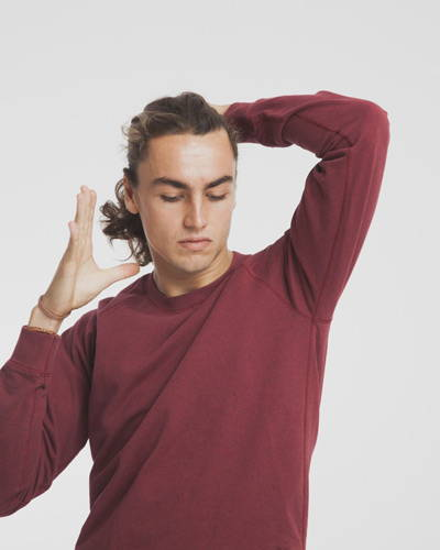 Man wearing burgundy red organic cotton sweatshirt tying up his hair