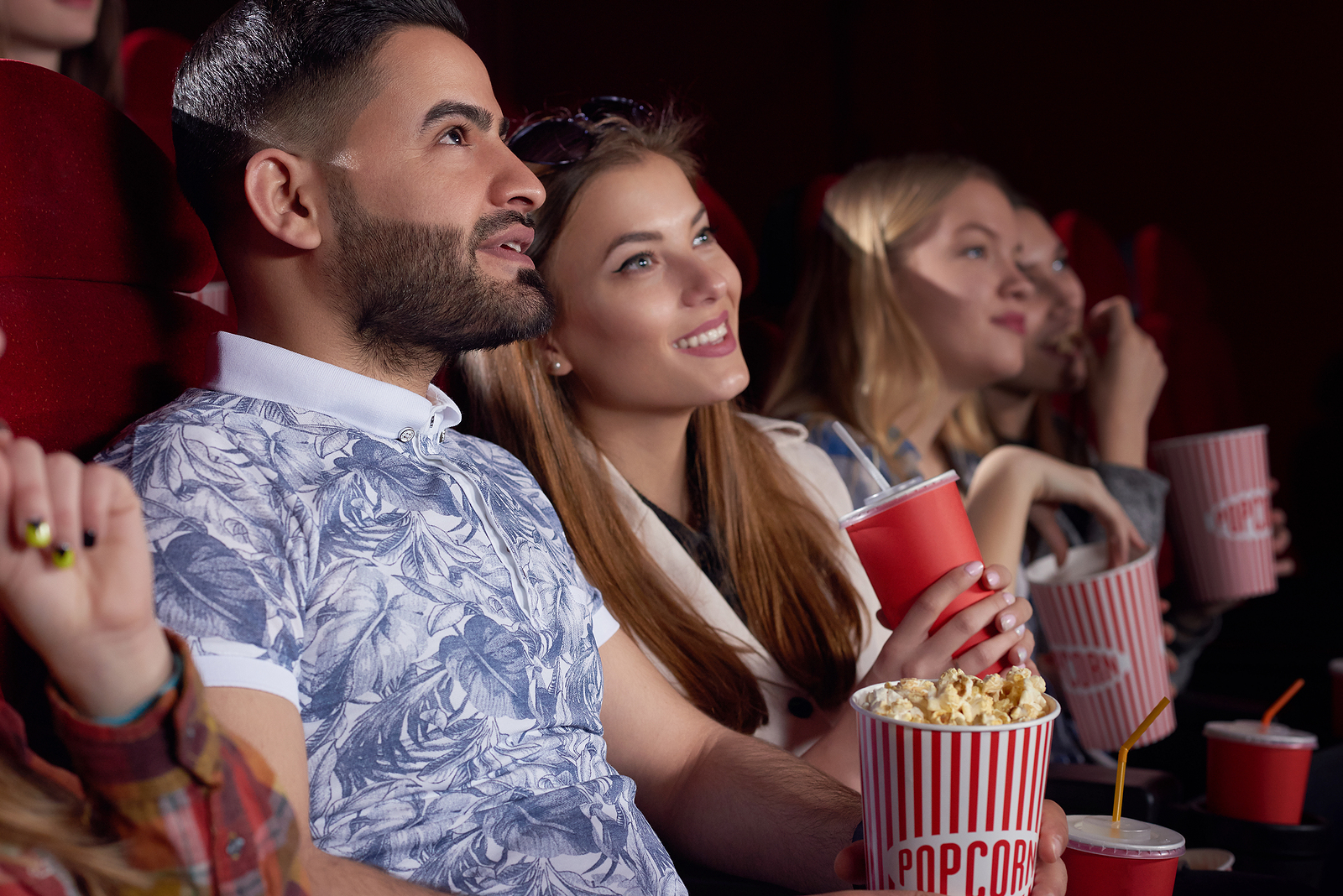 Couple watching a movie together smiling together with popcorn.