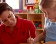 Preview image of a video featuring a Primrose teacher smiling as she looks at her student writing