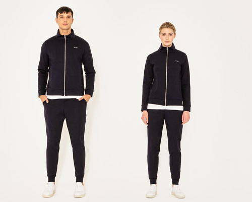 Man and woman wearing matching black zip up track jackets in black and sweatpants from sustainable streetwear brand Riley Studio