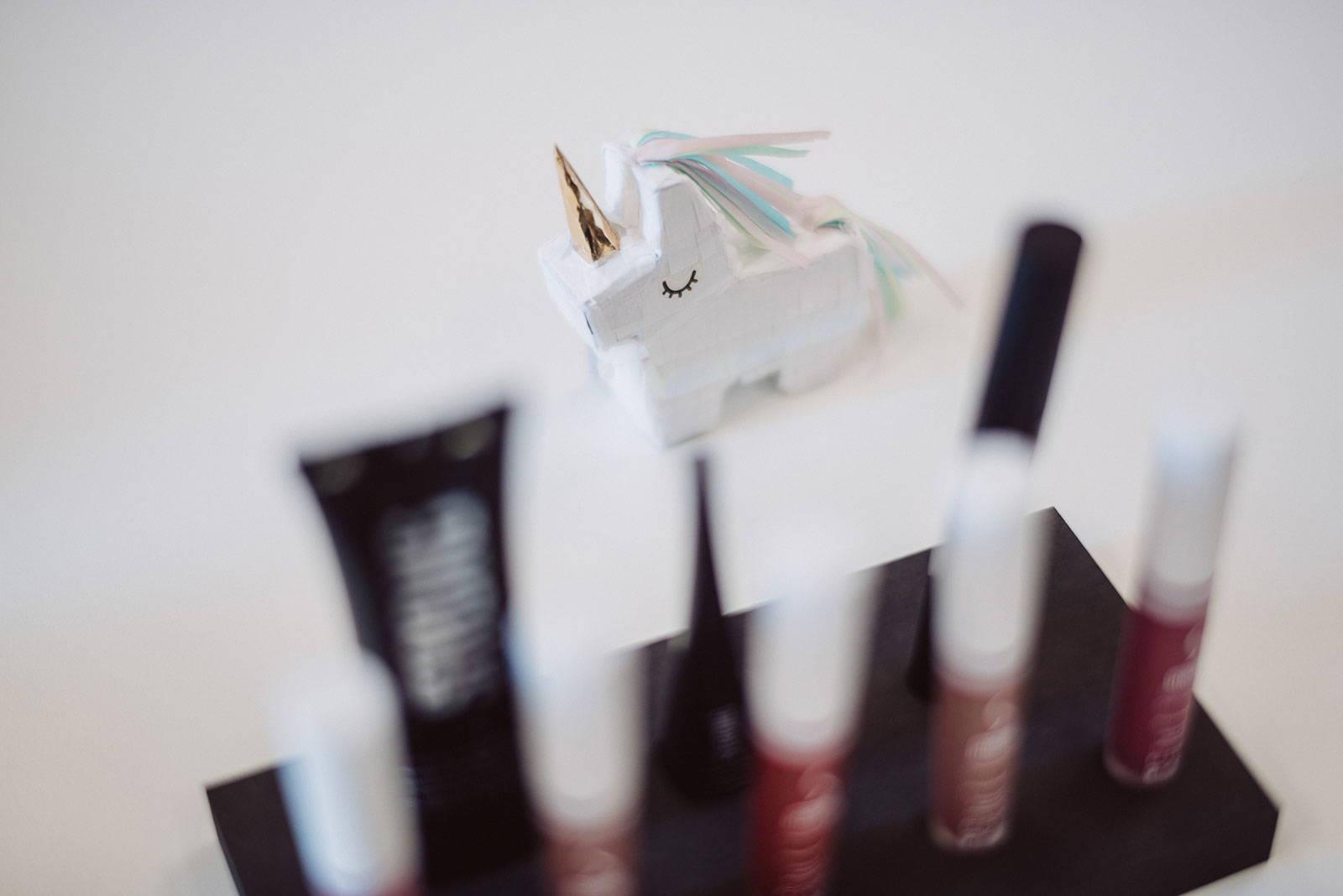 Einhorn Figur steht hinter verschwommenen Make-Up Produkten