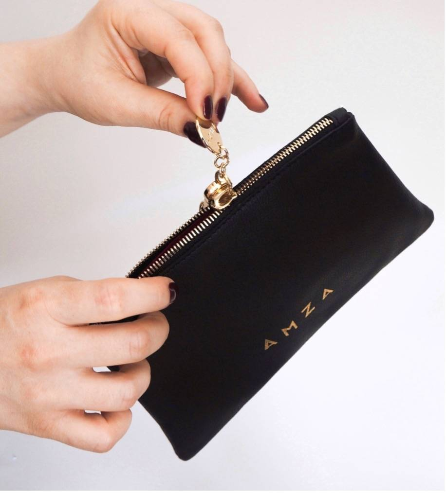 Close-up with woman hands opening the black Volterra pouch
