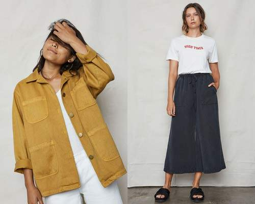 Woman wearing a washed yellow hemp and organic cotton chore workwear jacket with metal buttons and white vest underneath and woman wearing white organic cotton t-shirt with red printed logo reading 'High Times' with dark navy Tencel wide leg pants and black slip on sandals