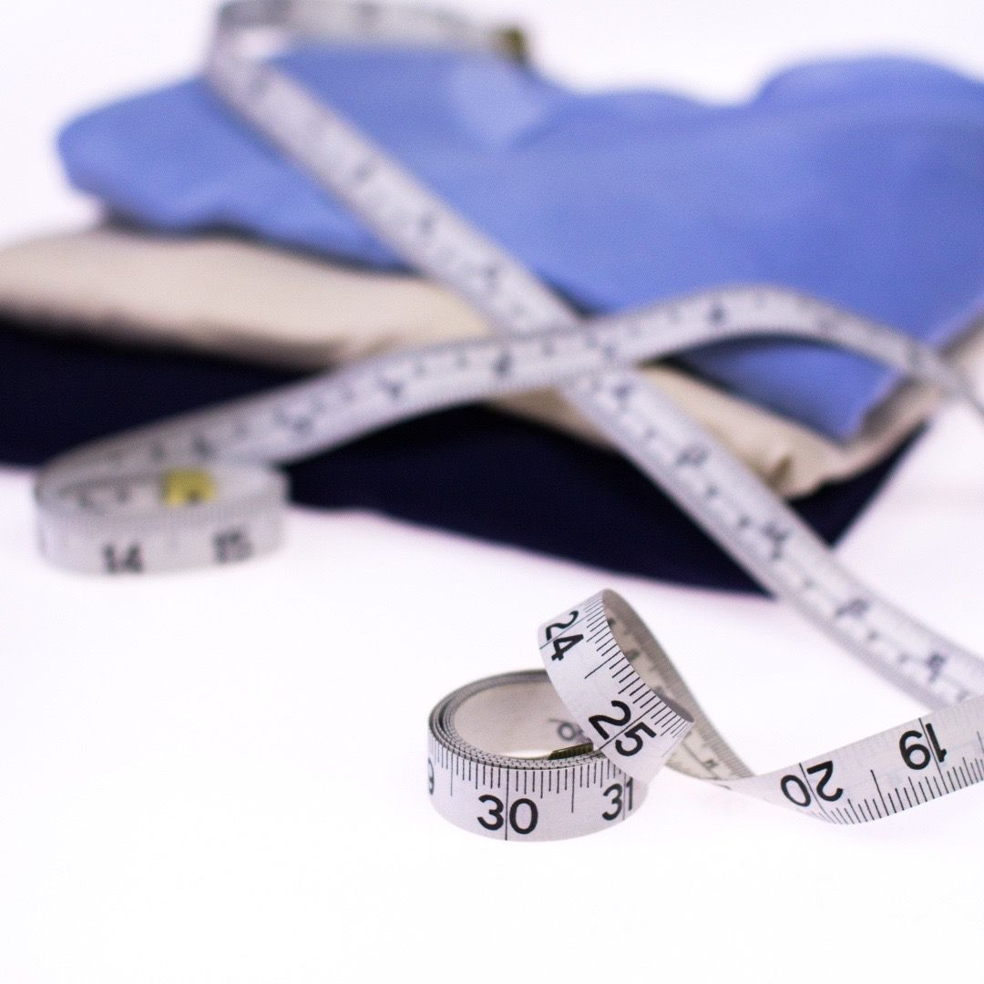 Undershirts folded on a table with a couple of tailors tape measures ontop