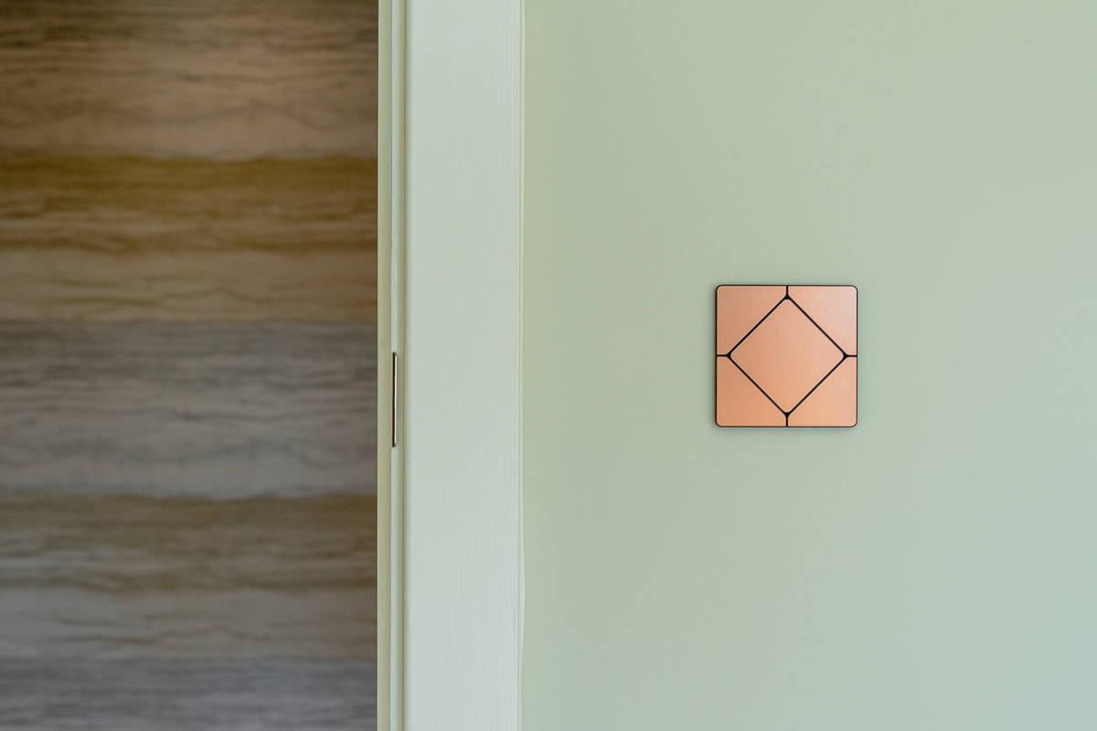 Faradite TAP-Lichtschalter in gebürstetem Kupfer auf einem Loxone Smart-Home
