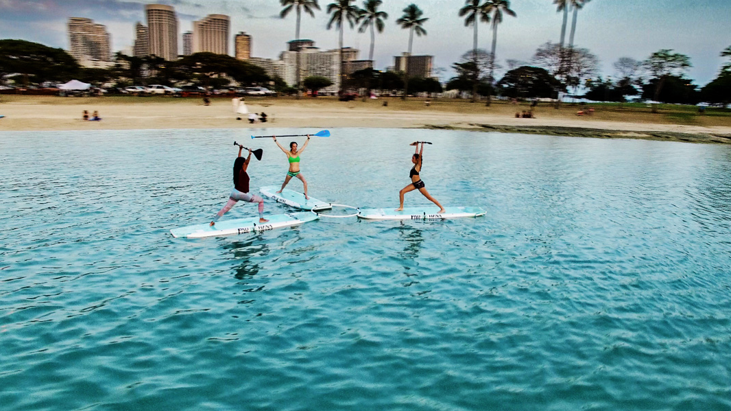 Practicing Lotus SUP yoga at sunset at Ala Moana beach park