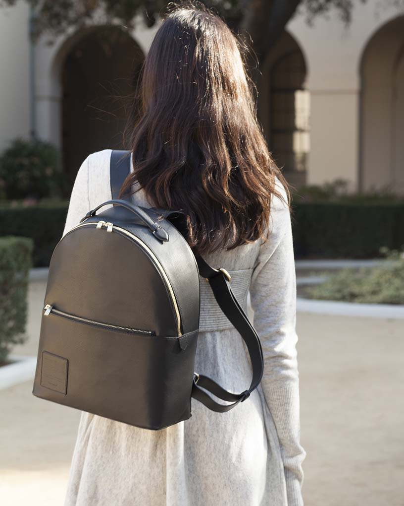Woman in grey dress carrying an Opus Mind black bag to go to the university