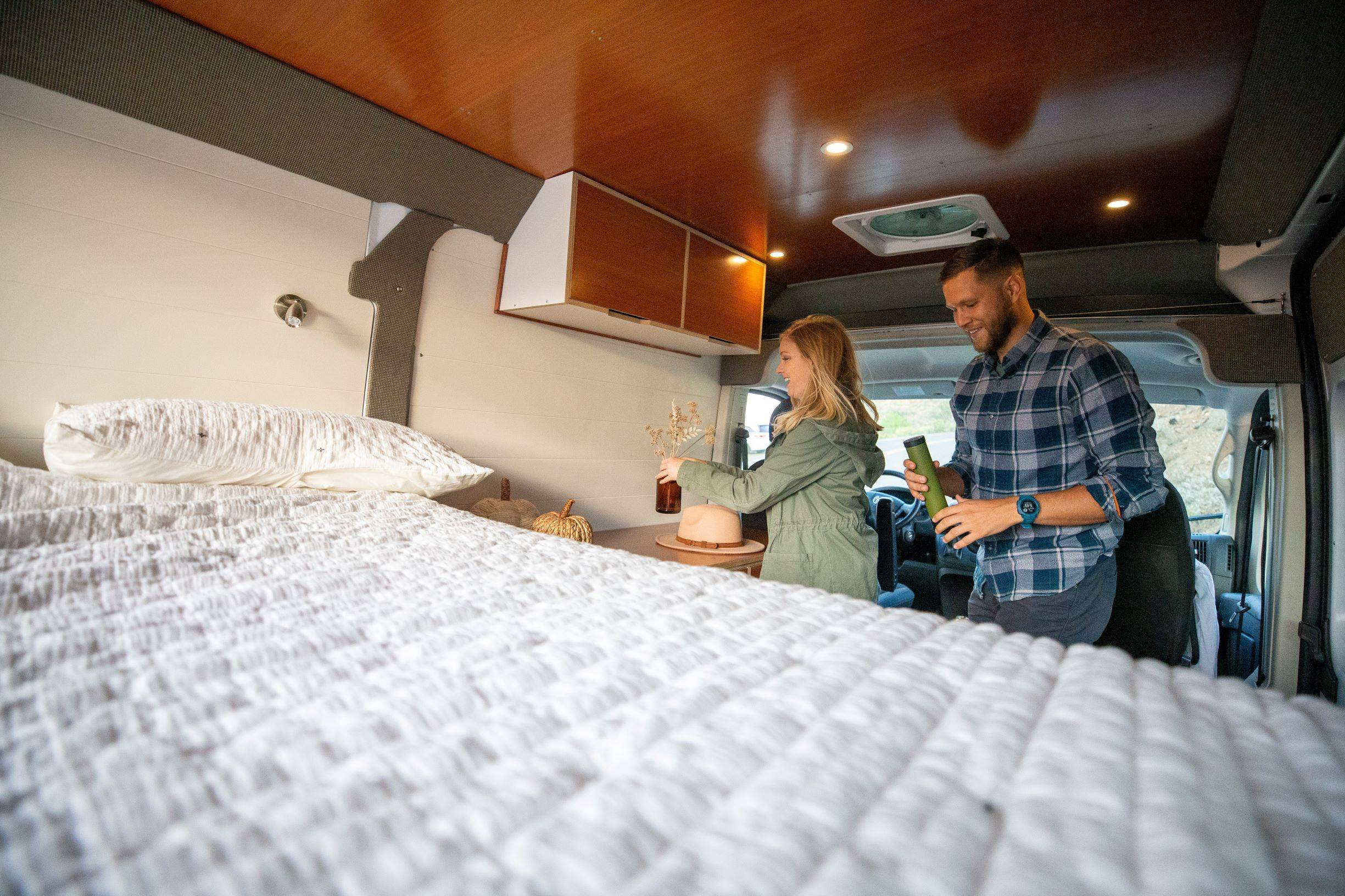 The Bivy - Sprinter 144 / ProMaster 136 Van Conversion - Interior View from Bed of Man and Woman - The Vansmith