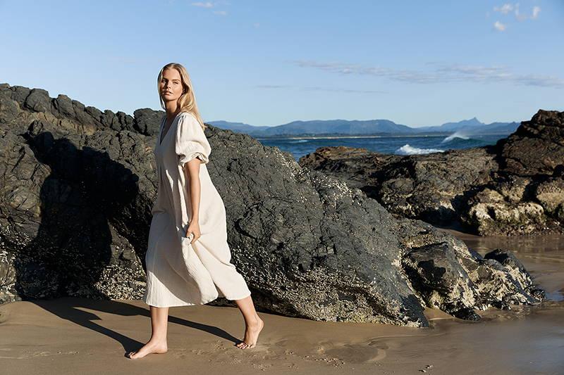 beautiful blonde woman walking barefoot on wet sand wearing loose linen dress