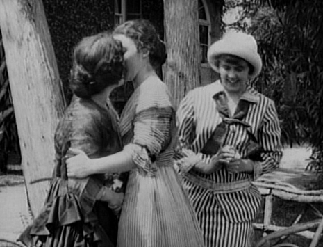 """Image of a same sex kiss in """"A Florida Enchantment"""" the image is in black and white, with the women wearing long dress suits."""