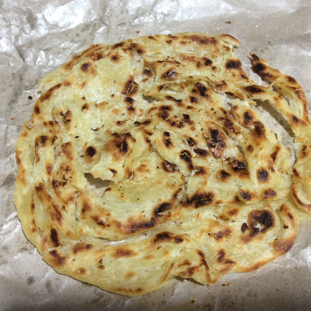 I make this Roti canai, used grace's recipe, and I did it once without any reduction. Was really happy, 1 time pass, taste is crispy a bit flaky delicious ,This is the recipe I'm looking for. The recipe is awesome. I want to share something of this recipe , I got adding some  marjerin and a little big of shortening , I'm using hand mixed mix up the dough is more fast, after direct split out 12 pcs small dough, I'm double up the recipe, after just leave it rest , coz I was busy go make other thing, after around 1 hour coming back roll up put in container mix up Vegi oil and marjerin, cover keep refrigerated, just few hours , I'm making out the roti canai is really really nice.....