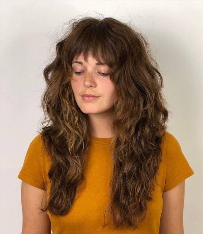 Woman with a long shaggy haircut and auburn hair