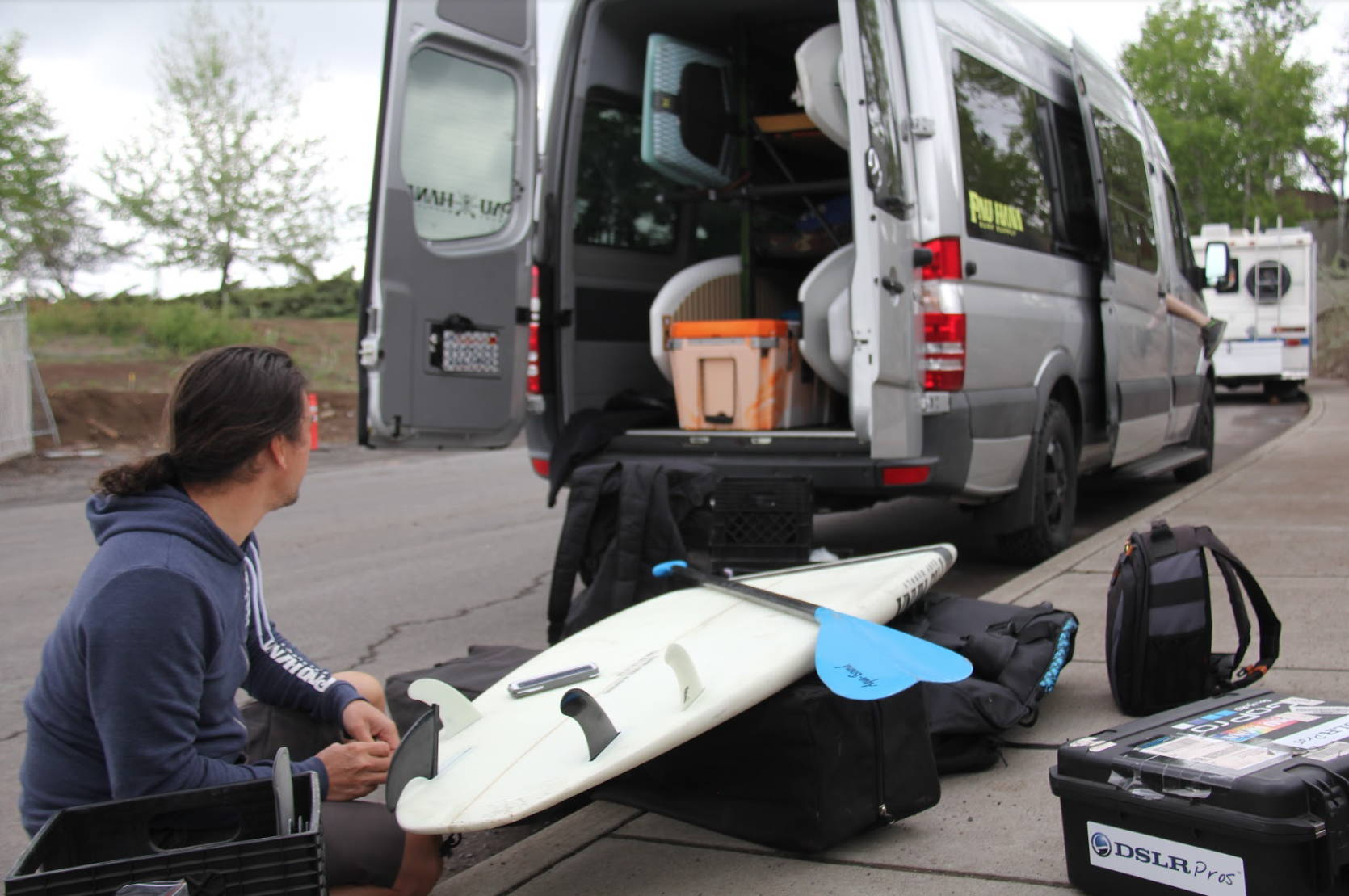 Todd loading up the Pau Hana surf supply van with carve boards and paddles to surf on the white water wave