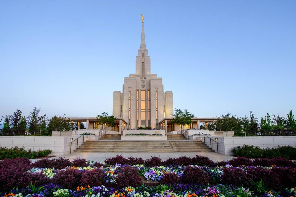 LDS art photo of the Oquirrh Mountain Temple among a lush array of flowers.