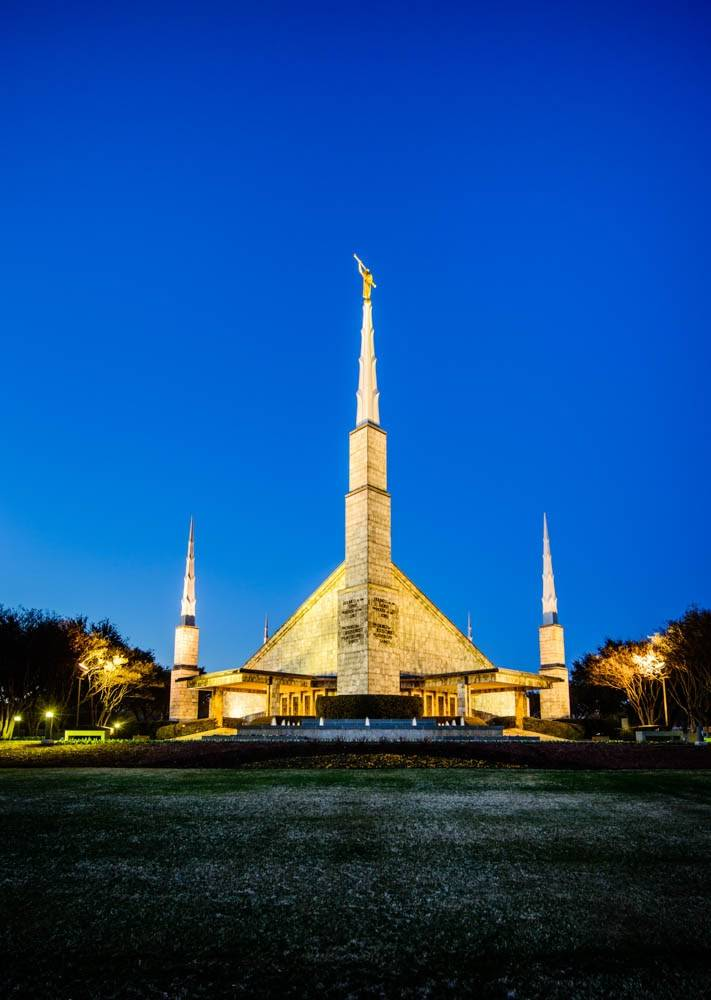 Dallas Temple glowing  against a deep-blue sky.