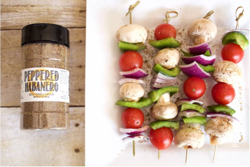 A bottle of FreshJax Organic Peppered Habanero Seasoning next to a plate of cooked veggie kabobs.