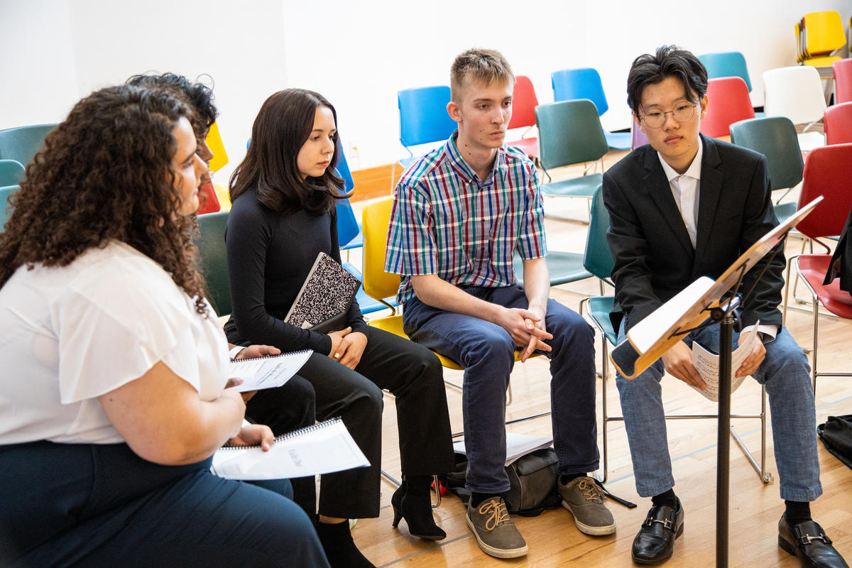 A group of young LA Phil composer fellows examines a music stand