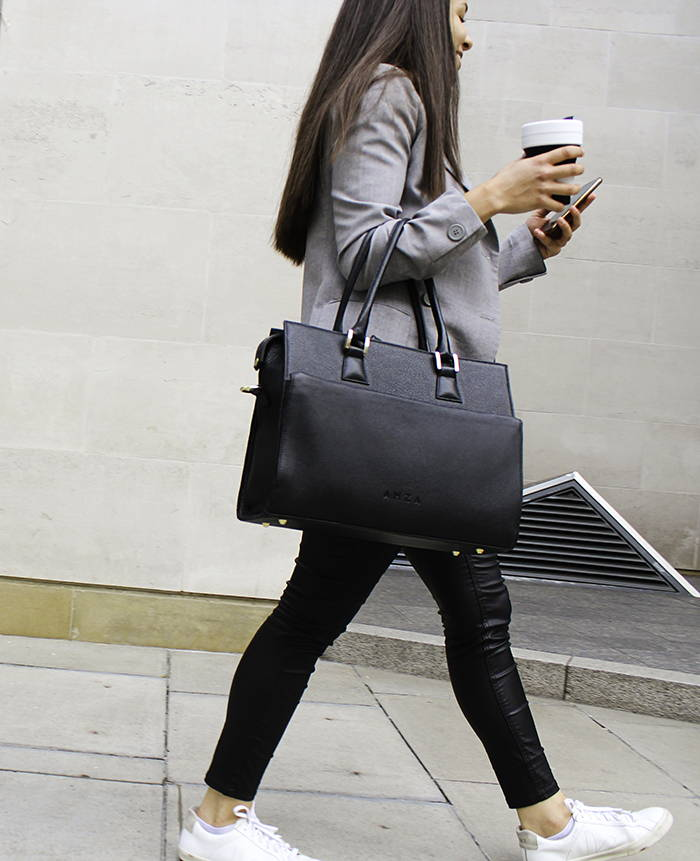 Woman looking at her phone, with her laptop bag on the arm while holding a cup of coffee