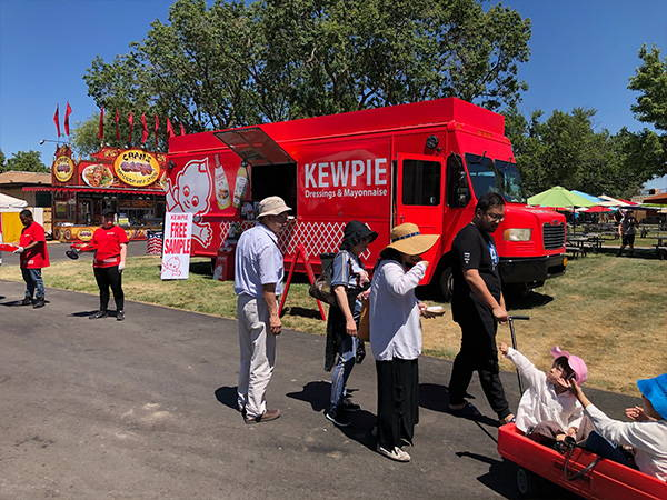 Kids in a wagon come to the Kewpie truck