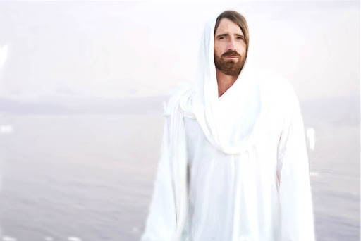 Jesus in a white robe standing in front of a calm body of water.