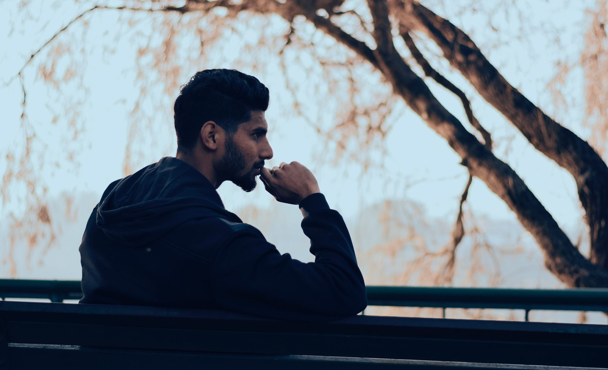 Silhouette of a man with a beard sitting on a park bench with a pensive look on his face and his hand on his chin.