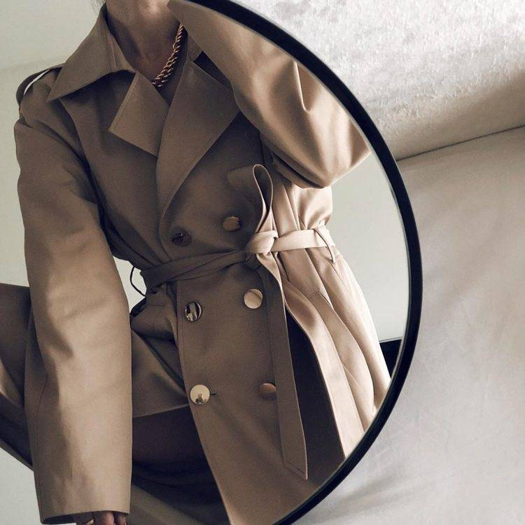 a woman with trench coat in front of a mirror