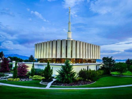 Provo Temple against a blue sky surrounded by deep green grass.