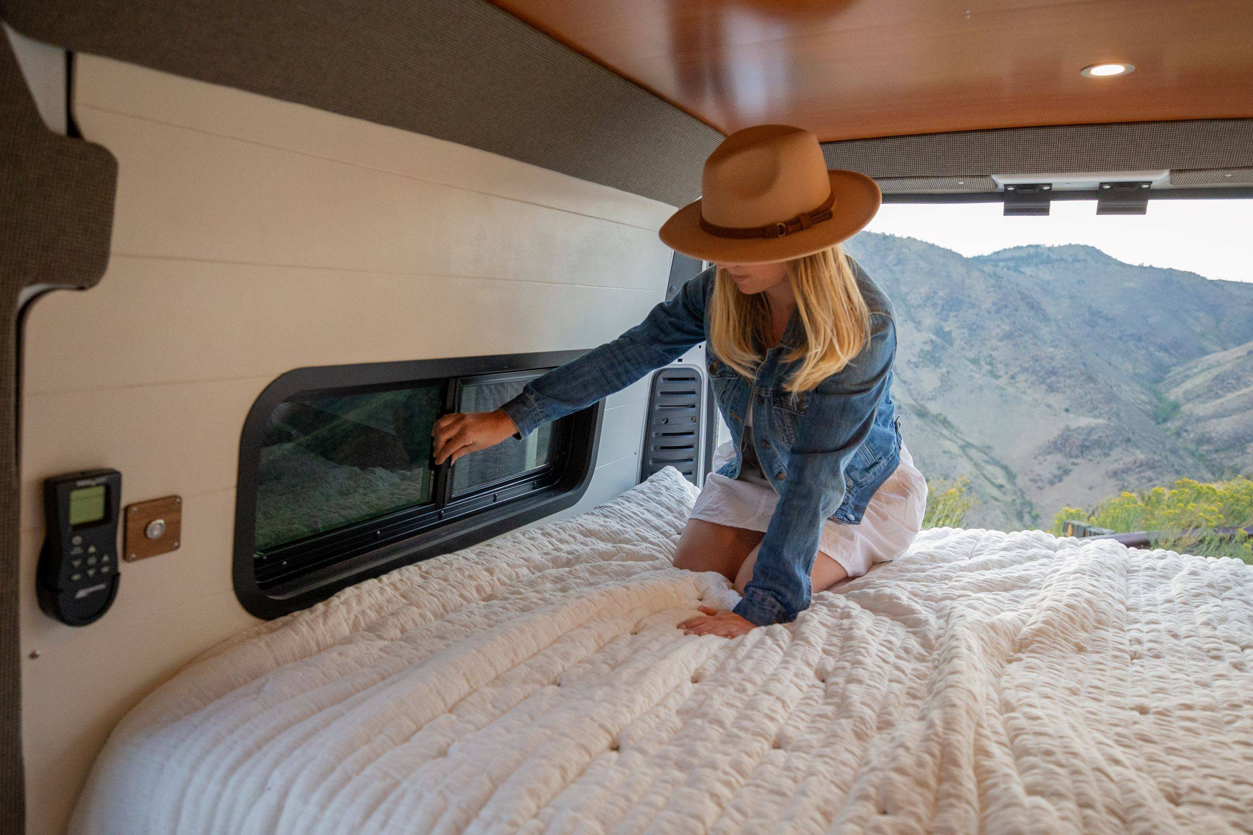 The Bivy - Sprinter 144 / ProMaster 136 Van Conversion - Woman in Bed Opening Bunk Window with Great View - The Vansmith