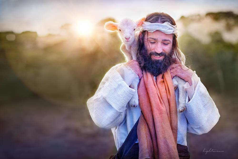 Image of Jesus carrying a lamb on His shoulders against the rising sun.