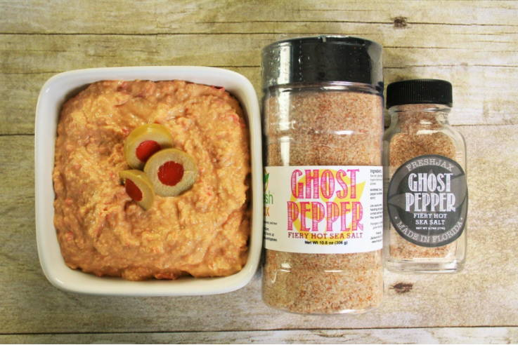 A bowl of spicy olive hummus next to a large and small bottle of FreshJax Organic Ghost Pepper Fiery Hot Sea Salt.