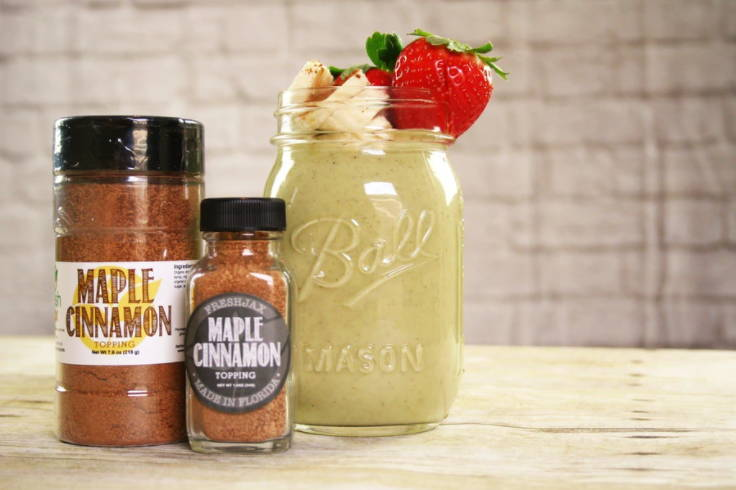 Two bottles of FreshJac Organic Maple Cinnamon Topping next to a Ball Jar filled with a maple cinnamon smoothie topped with whipped cream and strawberries.