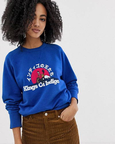 Front of woman wearing bright blue organic cotton sweatshirt with printed design from sustainable fashion brand Kings Of Indigo